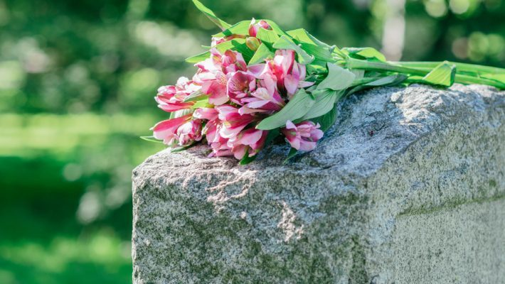 Flowers resting on a gravestone | CFHP